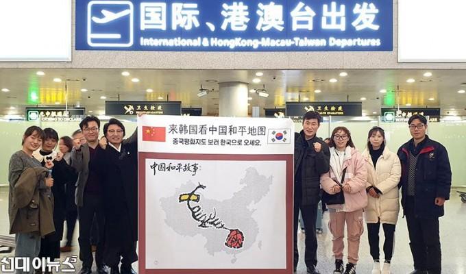 (가운데 왼쪽 첫 번째) 한한국 교수 일행과 중국인들이 중국 상하이 공항에서 _중국평화지도 보러 한국으로 오세요_ 라고 적힌 현수막을 ~.jpg